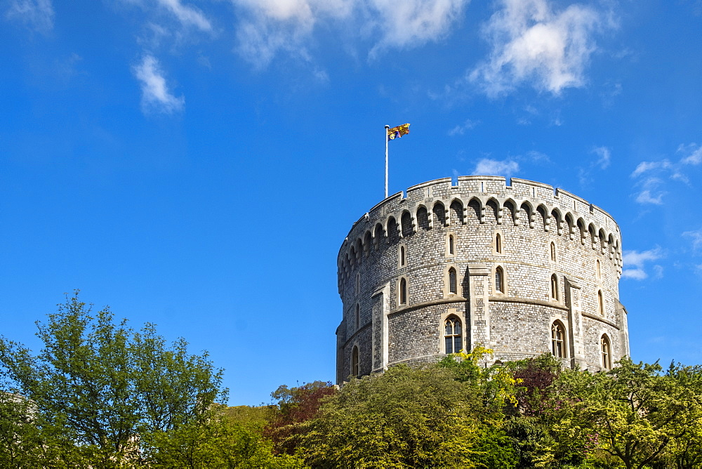 The round Norman Keep or Round Tower in Windsor Castle with the Queen's flag - the Royal Standard, flying