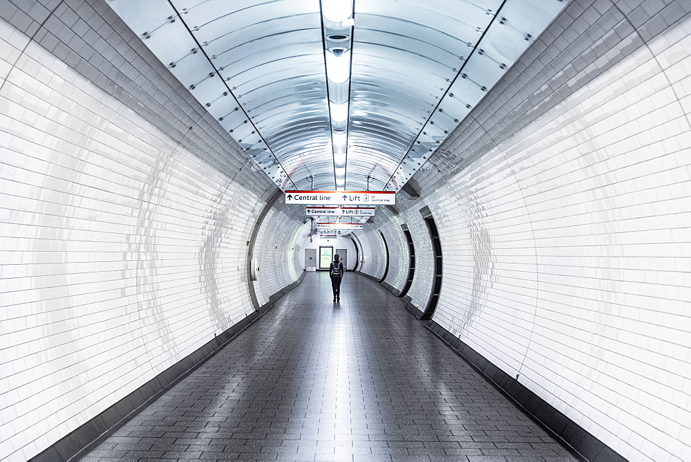 A single person walking along a corridor in an underground station during the Coronavirus lockdown, London, England, United Kingdom, Europe