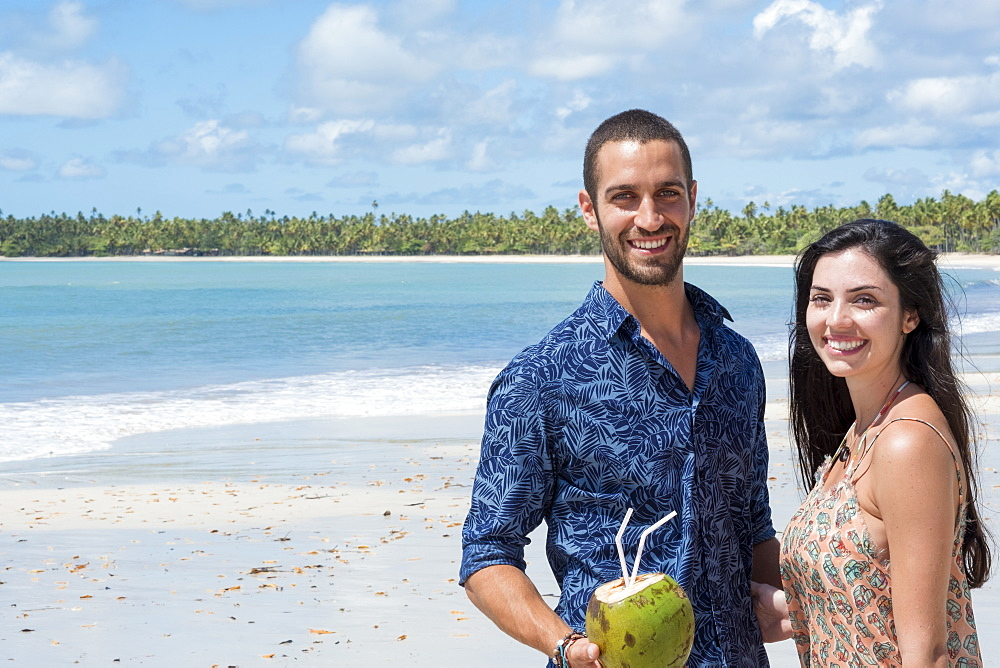 A good-looking Hispanic (Latin) couple smiling and standing together on a deserted beach, Brazil, South America