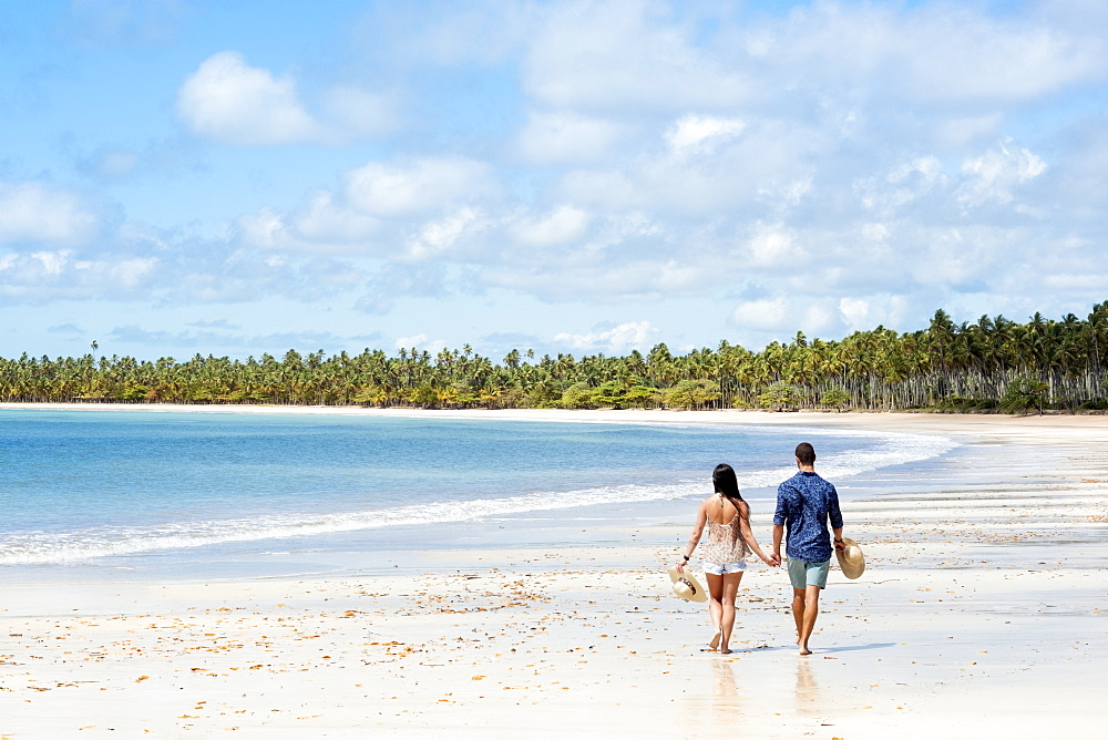 A good-looking Hispanic / Latin couple walking on a deserted beach with backs to camera and with copy space