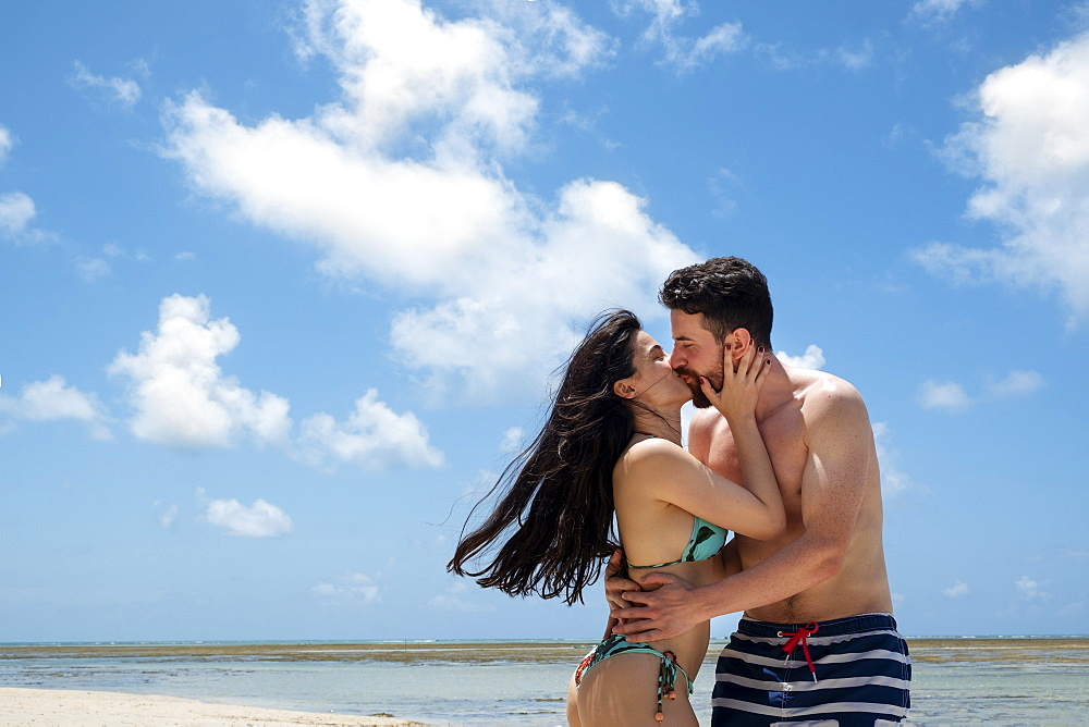 A young couple of Caucasian or Hispanic descent in their twenties wearing swimwear and kissing on a tropical beach. Copy Space