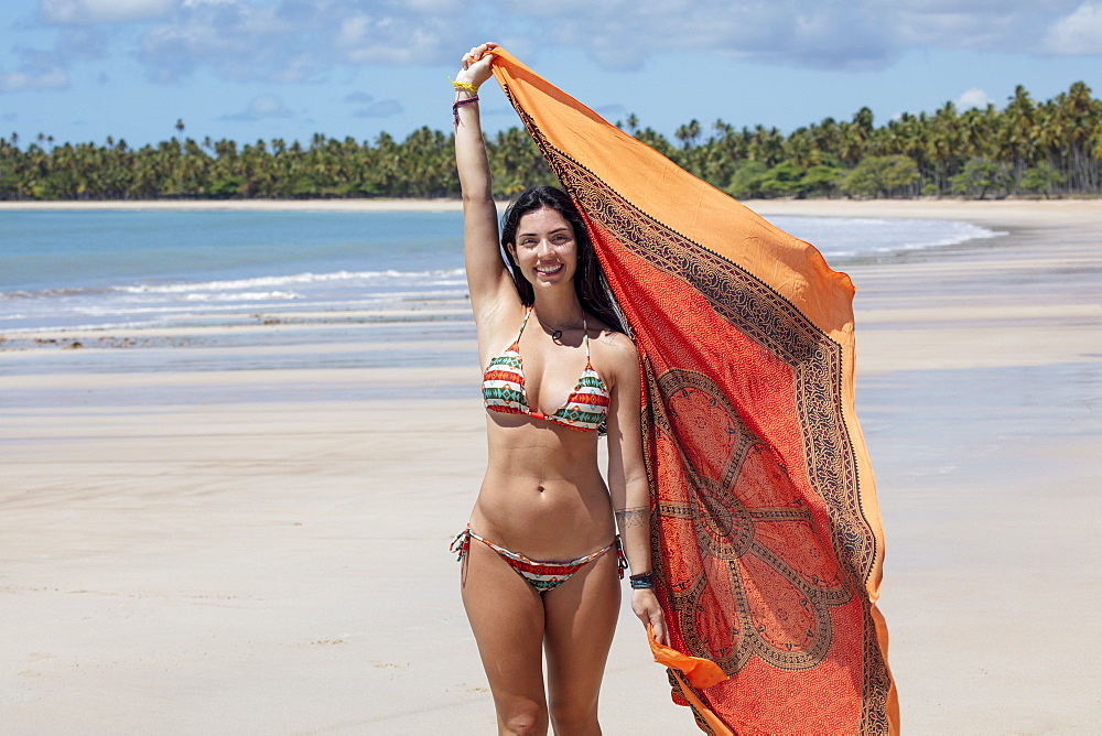 A beautiful Hispanic (Latin American) woman in her twenties smiling, holding a colourful shawl and standing on a deserted beach, Brazil, South America