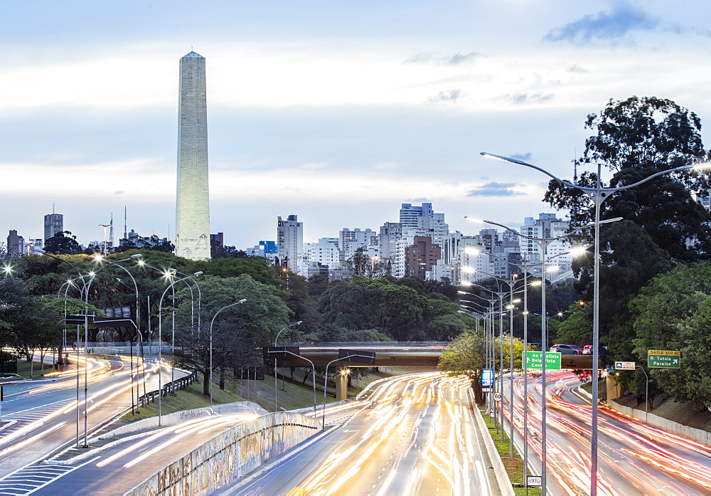 Rush hour traffic light trails on 23 de Maio Avenue, the skyline and the Obelisk of Heroes in Ibirapuera Park, Sao Paulo, Brazil, South America