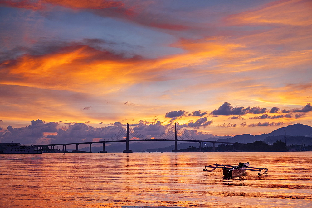 Indonesia, Maluku, Moluccas, Ambon, sunset over the harbour in Ambon city showing the suspension bridge and an outrigger boat - 1176-999