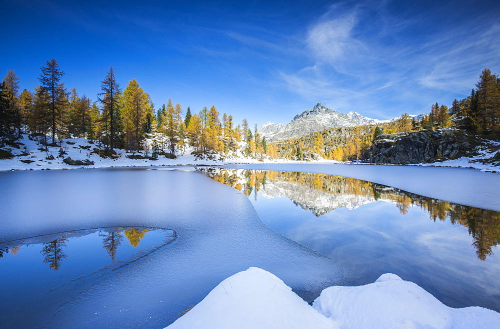 The peaks of Valmalenco in Valtellina reflecting in the water of the half frozen Lake Mufule, Lombardy, Italy, Europe