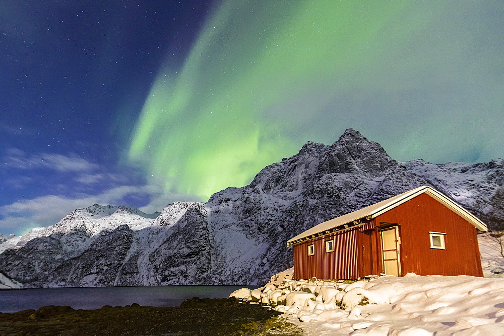 Northern Lights (aurora borealis) illuminate snowy peaks and the wooden cabin on a starry night at Budalen, Svolvaer, Lofoten Islands, Arctic, Norway, Scandinavia, Europe