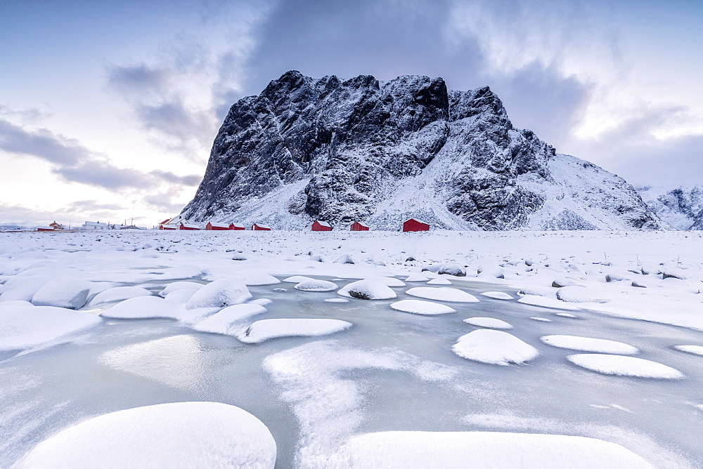 Snowy peaks and ice frame the typical fishermen houses called Rorbu, Eggum, Vestvagoy (Vest-Vagoy) Island, Lofoten Islands, Arctic, Norway, Scandinavia, Europe