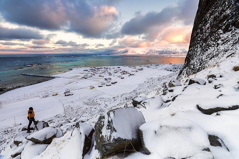 Photographer on the snow admires the fishing village under a colorful sky Eggum, Vestvagoy (Vest-Vagoy) Island, Lofoten Islands, Arctic, Norway, Scandinavia, Europe