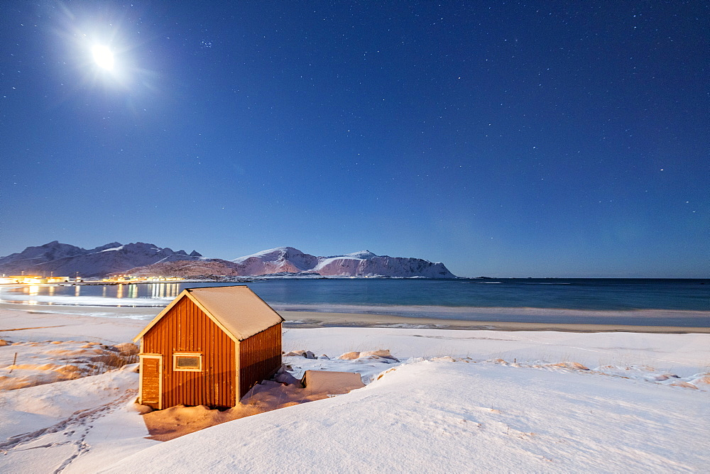 Moonlight on a typical fishermen cabin surrounded by snow, Ramberg, Flakstad, Nordland County, Lofoten Islands, Arctic, Norway, Scandinavia, Europe