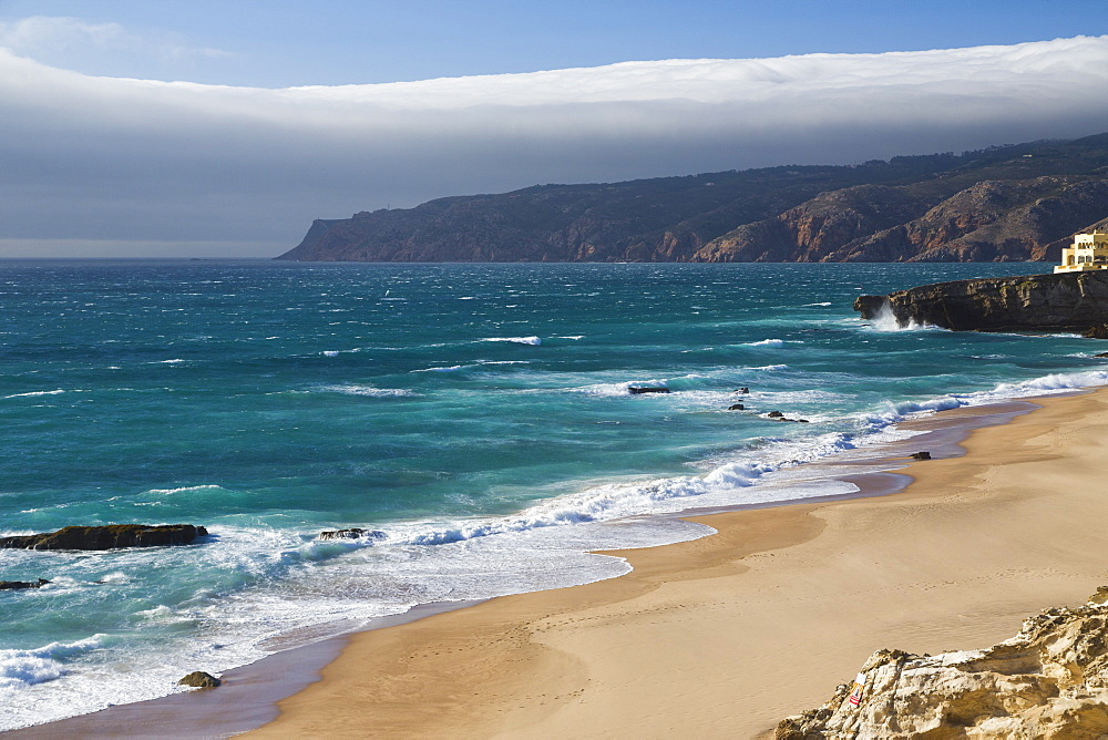 Ocean waves crashing on the sandy beach of Cascais, surrounded by cliffs, Estoril Coast, Lisbon, Portugal, Europe