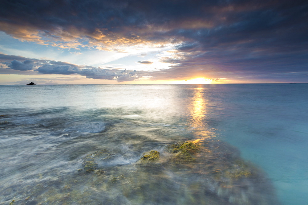 The lights of sunset are reflected in the blue sea, Hawksbill Bay, Antigua, Antigua and Barbuda, Leeward Islands, West Indies, Caribbean, Central America
