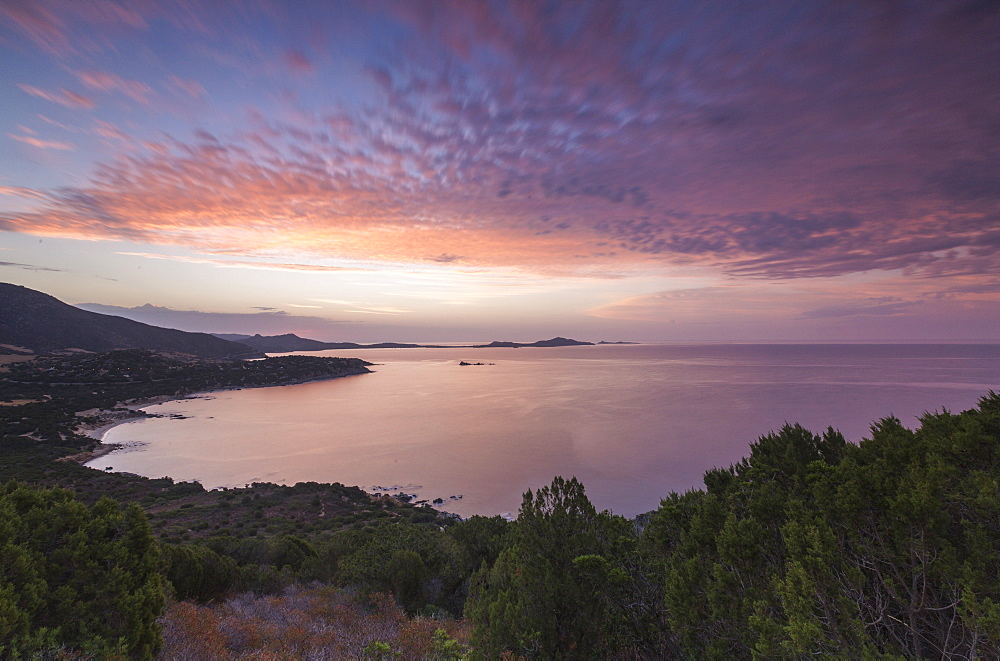 The colors of sunrise are reflected on the sea around the beach of Solanas, Villasimius, Cagliari, Sardinia, Italy, Mediterranean, Europe