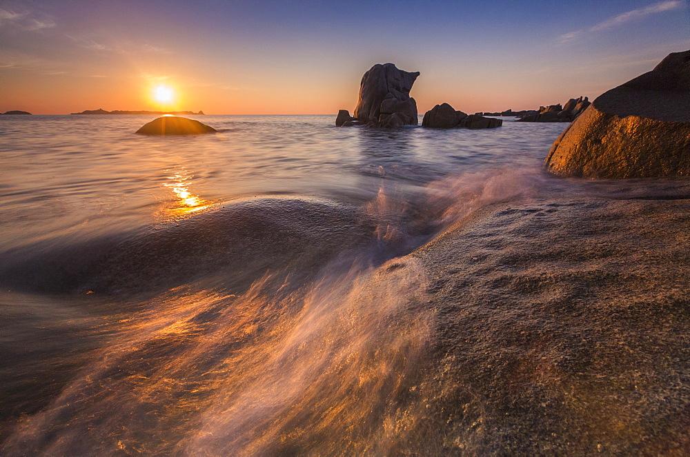 Waves crashing on cliffs under the fiery sky at sunrise, Punta Molentis, Villasimius, Cagliari, Sardinia, Italy, Mediterranean, Europe