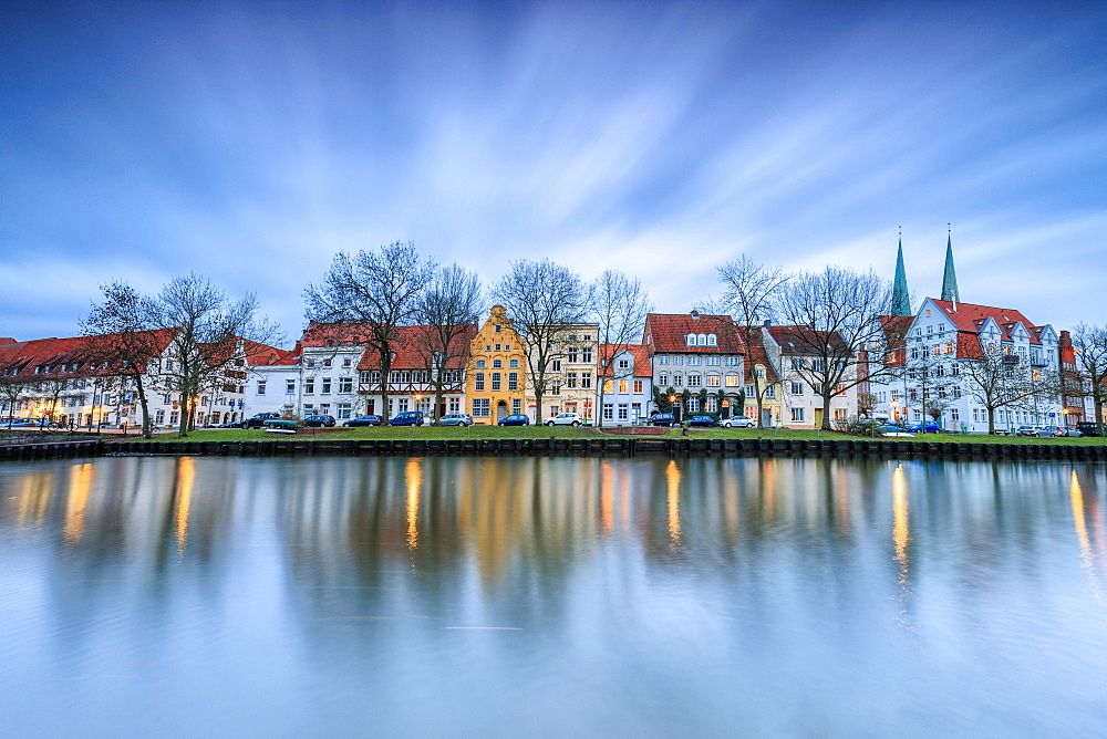 Clouds on the typical houses and towers of cathedral reflected in River Trave at dusk, Lubeck, Schleswig Holstein, Germany, Europe