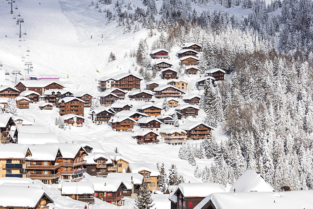Snowy woods frame the typical alpine village and ski resort, Bettmeralp, district of Raron, canton of Valais, Switzerland, Europe