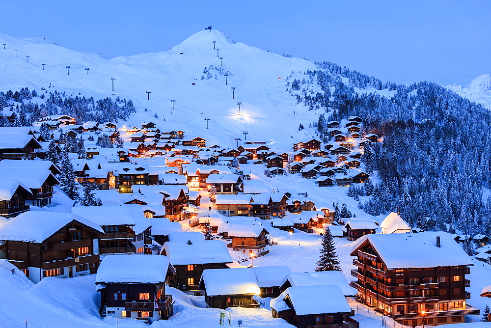 Blue dusk on the snowy alpine village surrounded by ski lifts, Bettmeralp, district of Raron, canton of Valais, Switzerland, Europe