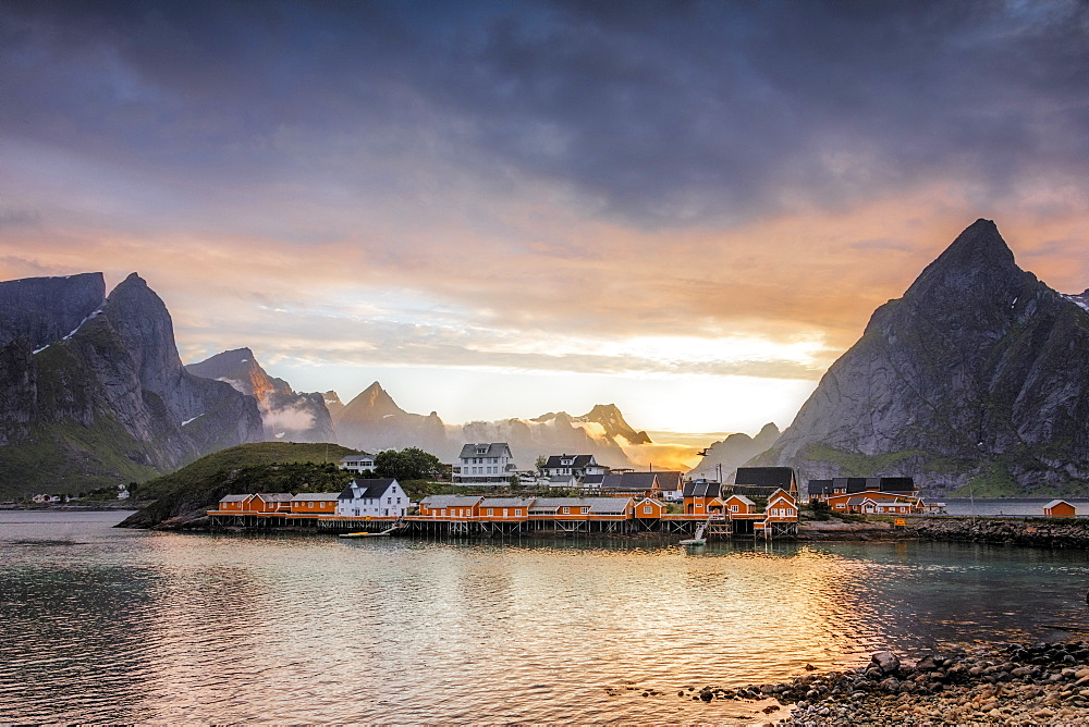 Sunset on the fishing village framed by rocky peaks and sea, Sakrisoya, Nordland county, Lofoten Islands, Arctic, Northern Norway, Scandinavia Europe