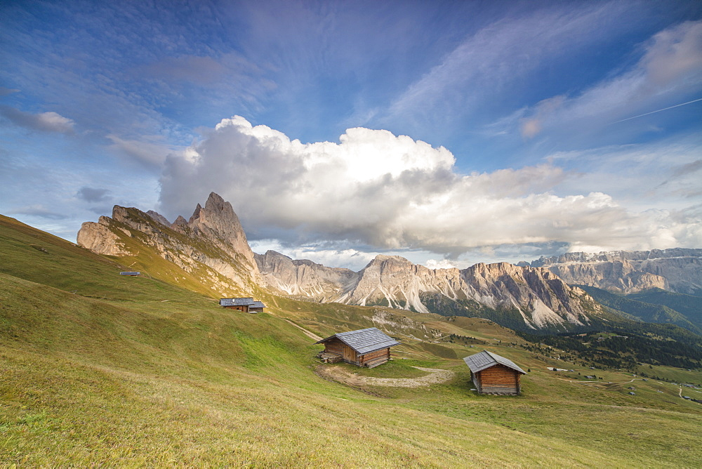 Sunset on the green meadows and huts of the Odle mountain range seen from Seceda Val Gardena Trentino Alto Adige Italy Europe