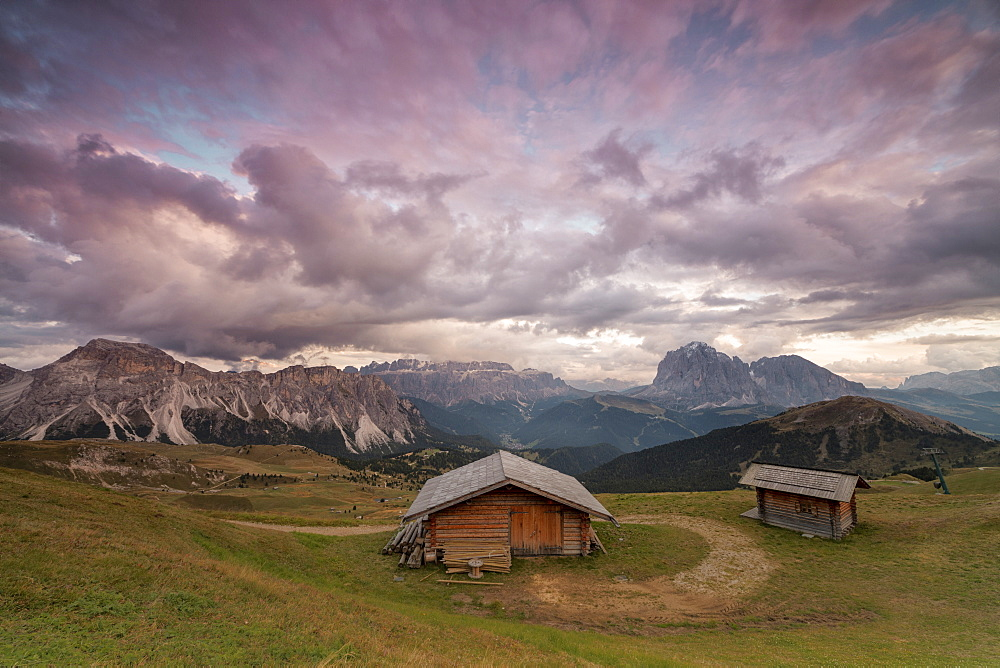 Pink clouds at sunset on the typical huts of Odle mountain range seen from Seceda Val Gardena Trentino Alto Adige Italy Europe