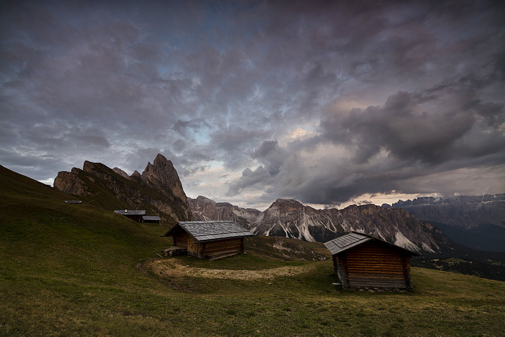 Dark clouds on green meadows and huts of the Odle mountain range seen from Seceda, Val Gardena, Trentino-Alto Adige, Italy, Europe