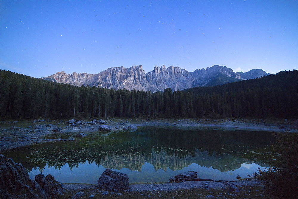 Latemar mountain range and woods are reflected in Lake Carezza at dusk Ega Valley Province of Bolzano South Tyrol Italy Europe