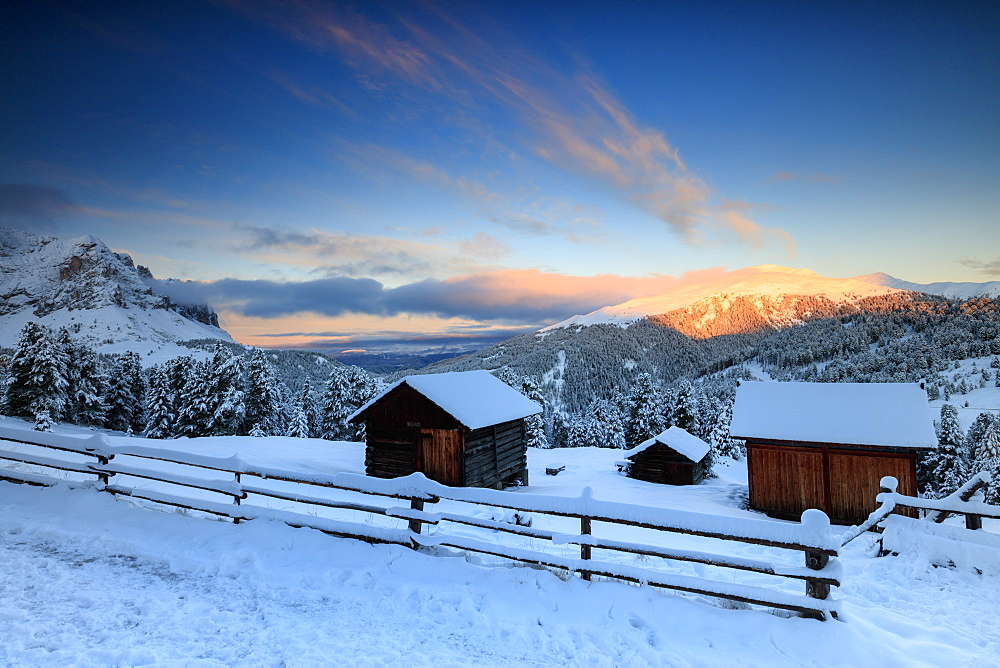 The sunrise lights up the snowy woods and huts Passo Delle Erbe Funes Valley South Tyrol Italy Europe