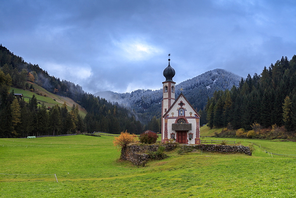 Clouds on Church of Ranui surrounded by meadows and woods in the fall, St. Magdalena, Funes Valley, South Tyrol, Dolomites, Italy, Europe