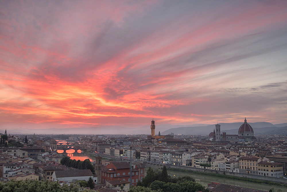 Pink clouds at sunset frame the city of Florence crossed by Arno River seen from Piazzale Michelangelo, Florence, Tuscany, Italy, Europe