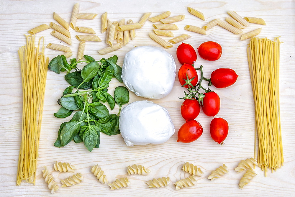 Composition with the bright colours of Italian food: pasta, spaghetti, tomatoes from Sicily, mozzarella from Naples and basil, Italy, Europe