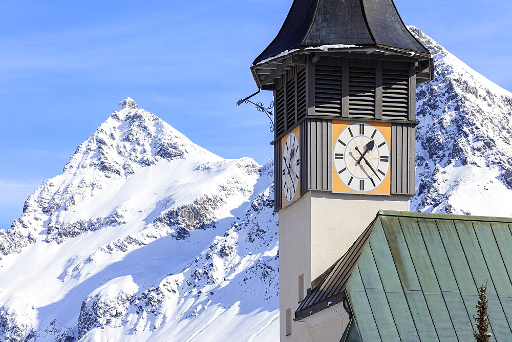 The typical alpine bell tower frames the snowy peaks, Langwies, district of Plessur, Canton of Graubunden, Swiss Alps, Switzerland, Europe