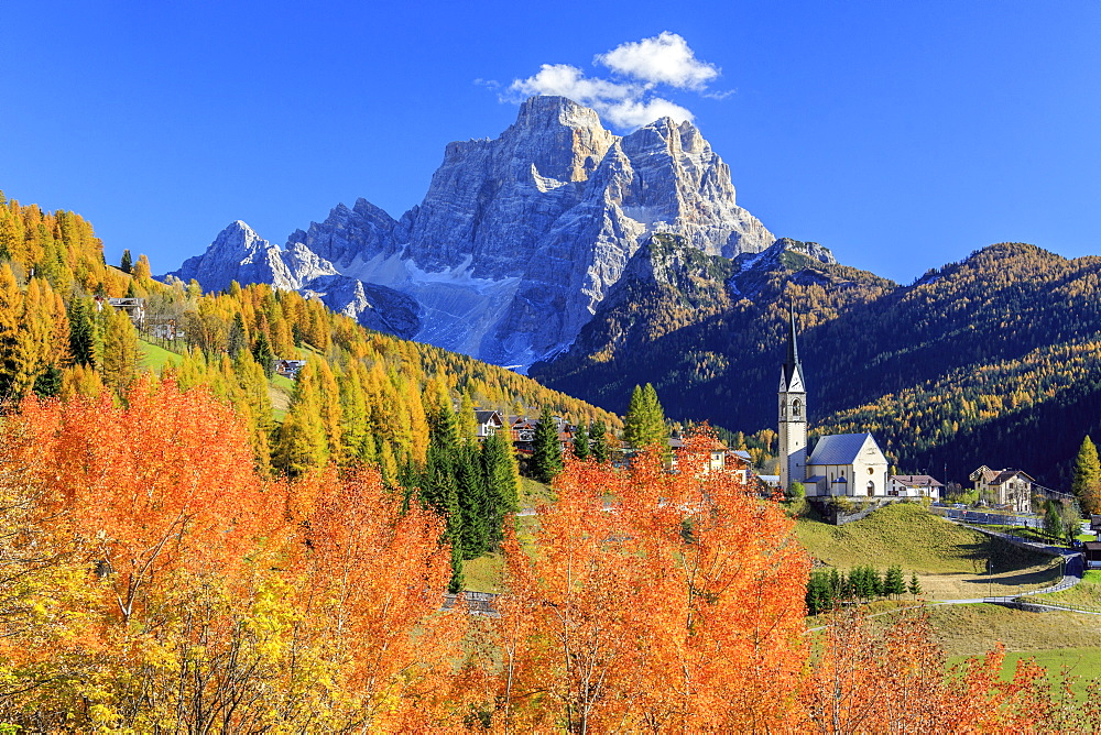 Red and orange trees with the tiny church of Selva di Cadore, in the Dolomites, with Mount Pelmo in the background, Veneto, Italy, Europe