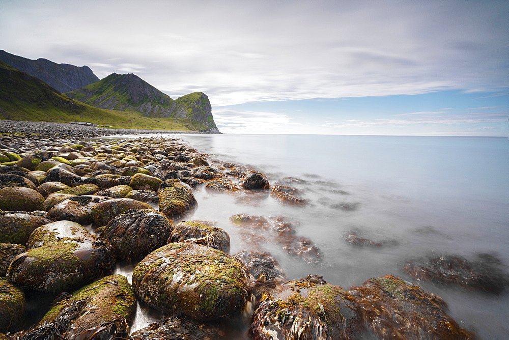 Rocks on the beach frame the calm clear sea, Unstad, Vestvagoy, Lofoten Islands, Norway, Scandinavia, Europe