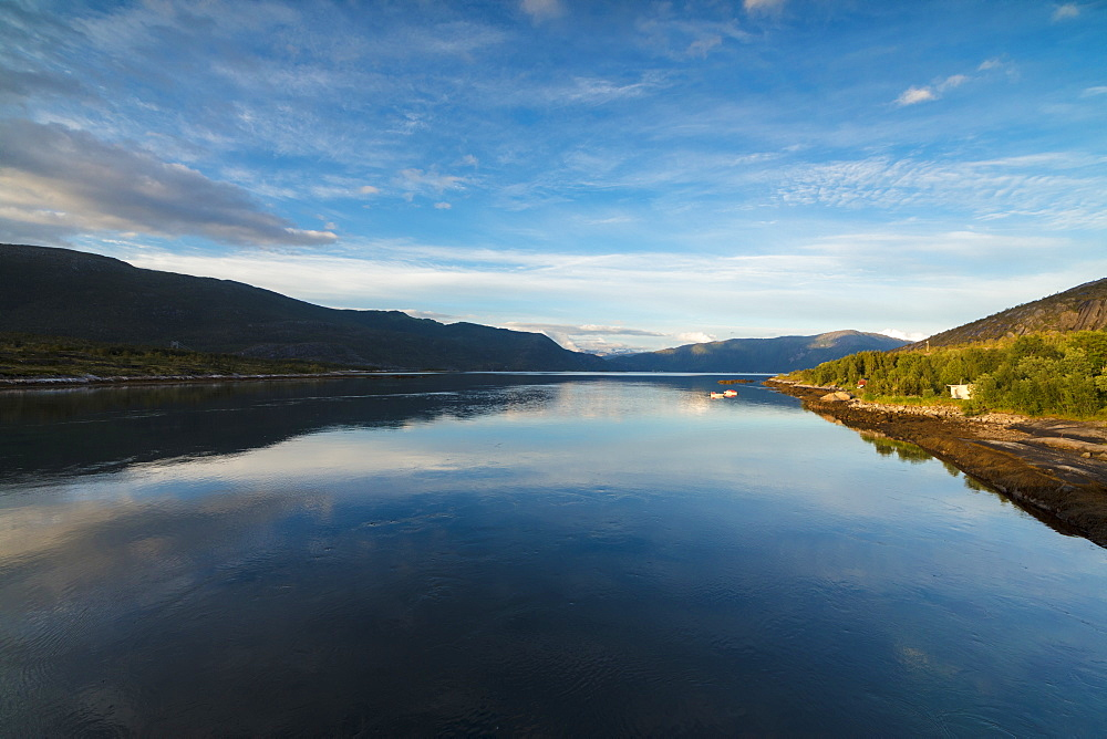 Lights of midnight sun illuminate the clear water of blue sea and green woods Anepollen Fjord Norway Europe