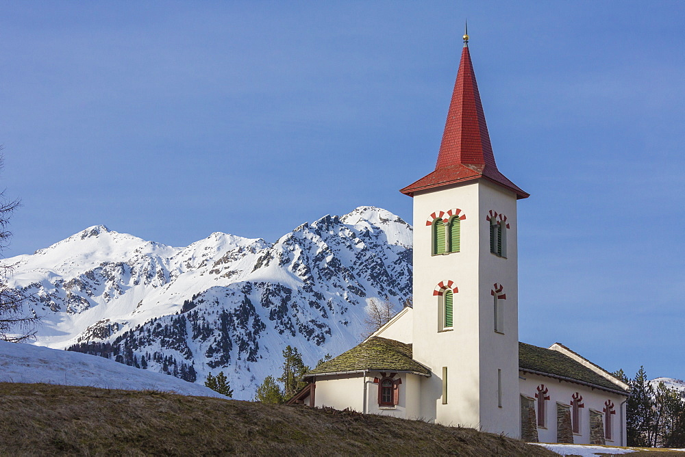 The white alpine church framed by snowy peaks Maloja Bregaglia Valley Canton of Graubünden Engadine Switzerland Europe