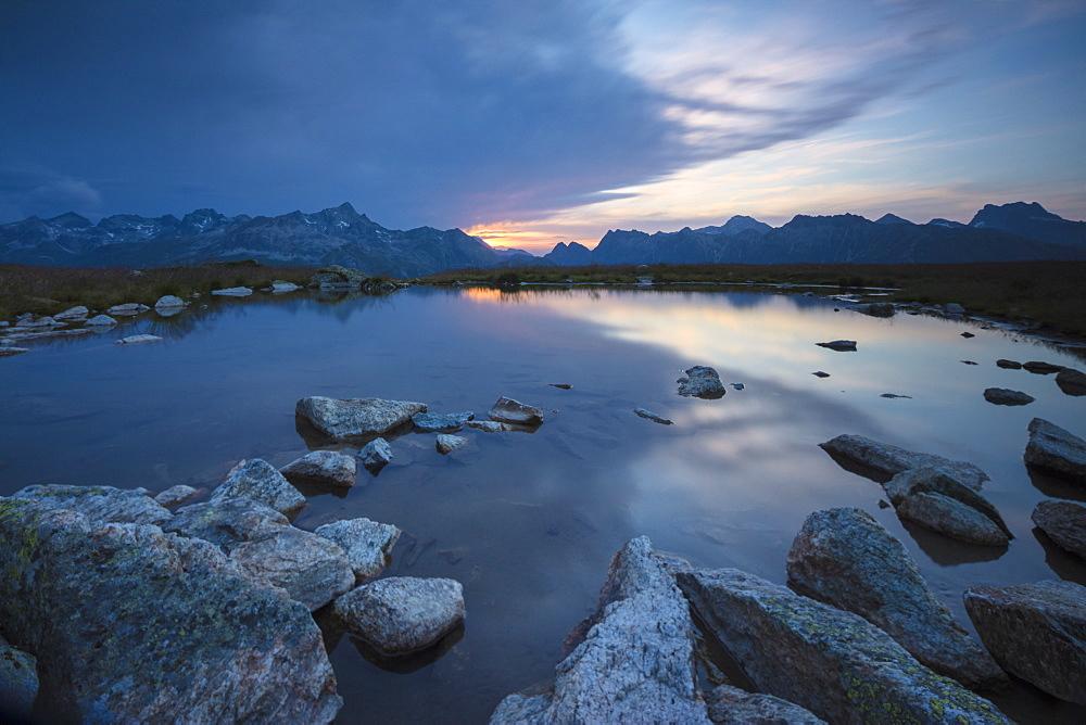 The lights of sunrise are reflected in the alpine lake Muottas Muragl Samedan Canton of Graubünden Engadine Switzerland Europe
