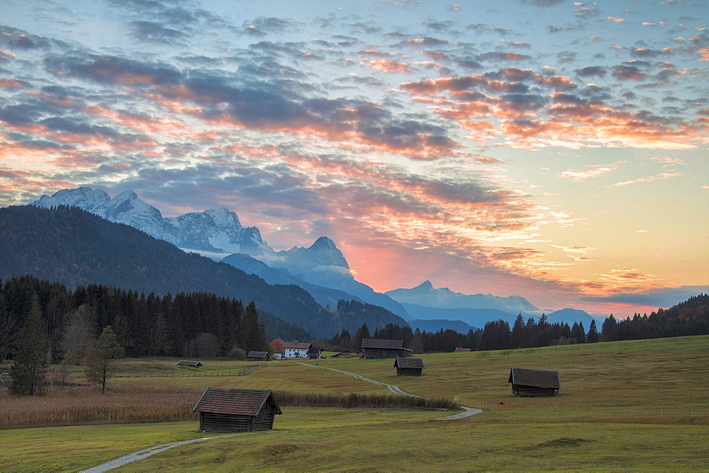 Sunset on wooden huts and meadows with the Alps in background, Geroldsee, Krun, Garmisch Partenkirchen, Upper Bavaria, Germany, Europe