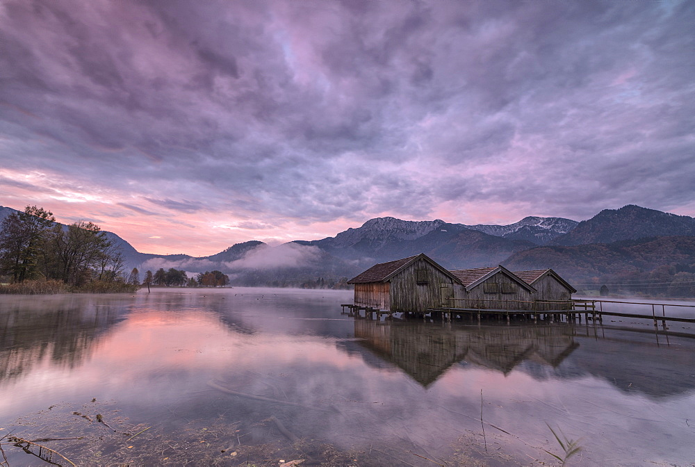 Purple sky at sunset and wooden huts are reflected in the clear water of Kochelsee Schlehdorf Bavaria Germany Europe