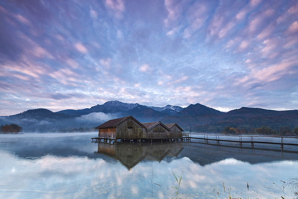 Pink clouds at sunset and wooden huts are reflected in the clear water of Kochelsee Schlehdorf Bavaria Germany Europe
