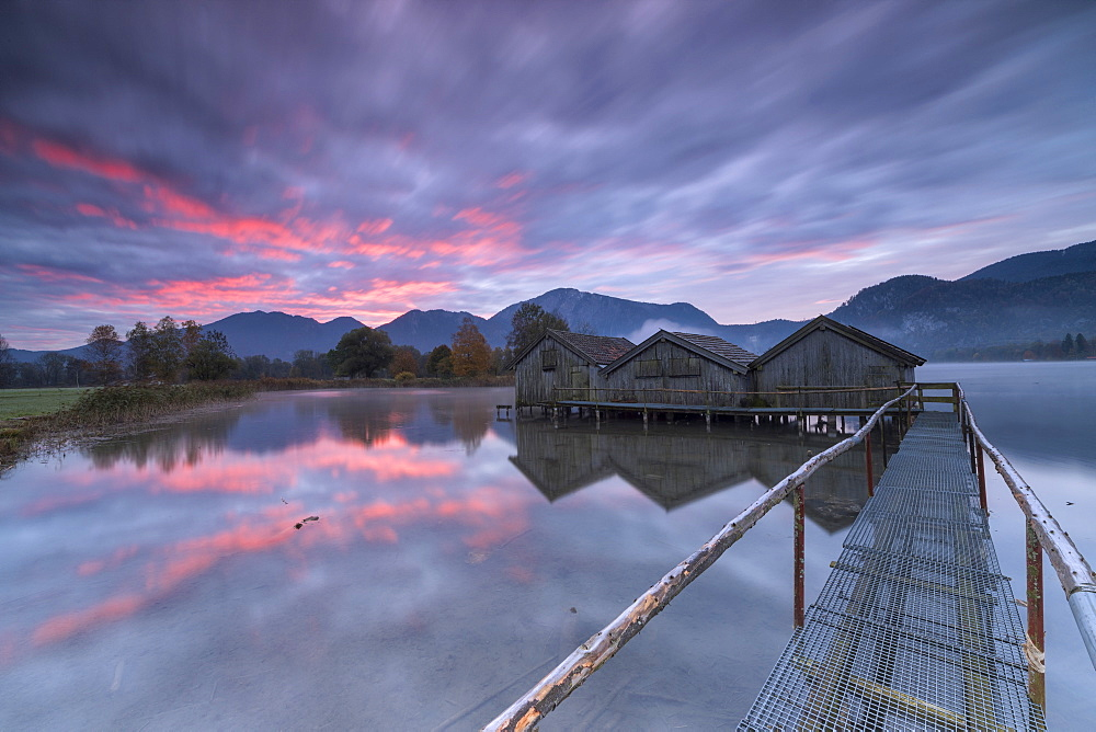 Purple sky at sunset and wooden huts are reflected in the clear water of Kochelsee, Schlehdorf, Bavaria, Germany, Europe