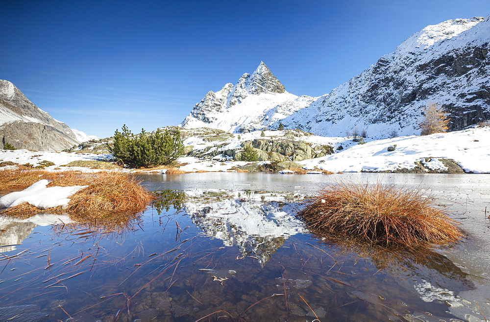 Snowy peaks are reflected in the alpine lake partially frozen Lejets Crap Alv canton of Graubunden Engadine Switzerland Europe
