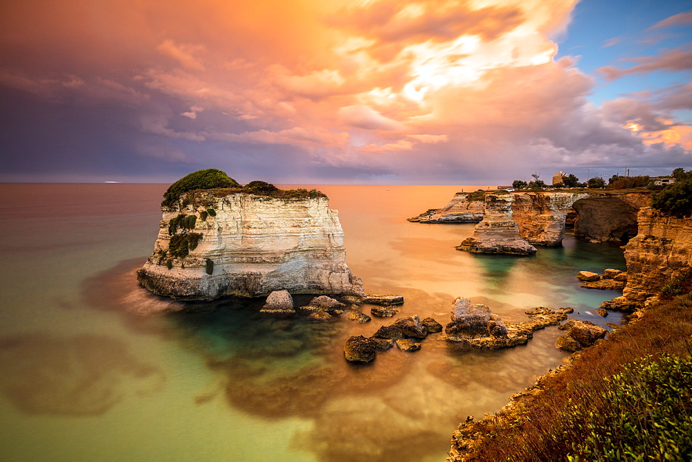 Sunset frames the high cliffs known as Faraglioni di Sant'Andrea and the turquoise sea, province of Lecce, Apulia, Italy, Europe