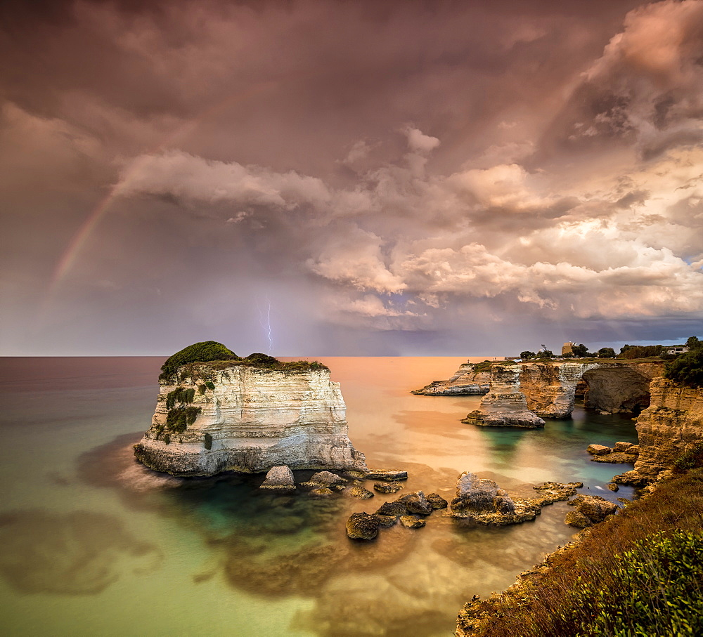 Rainbow and lightning after the storm on cliffs known as Faraglioni di Sant'Andrea, province of Lecce, Apulia, Italy, Europe