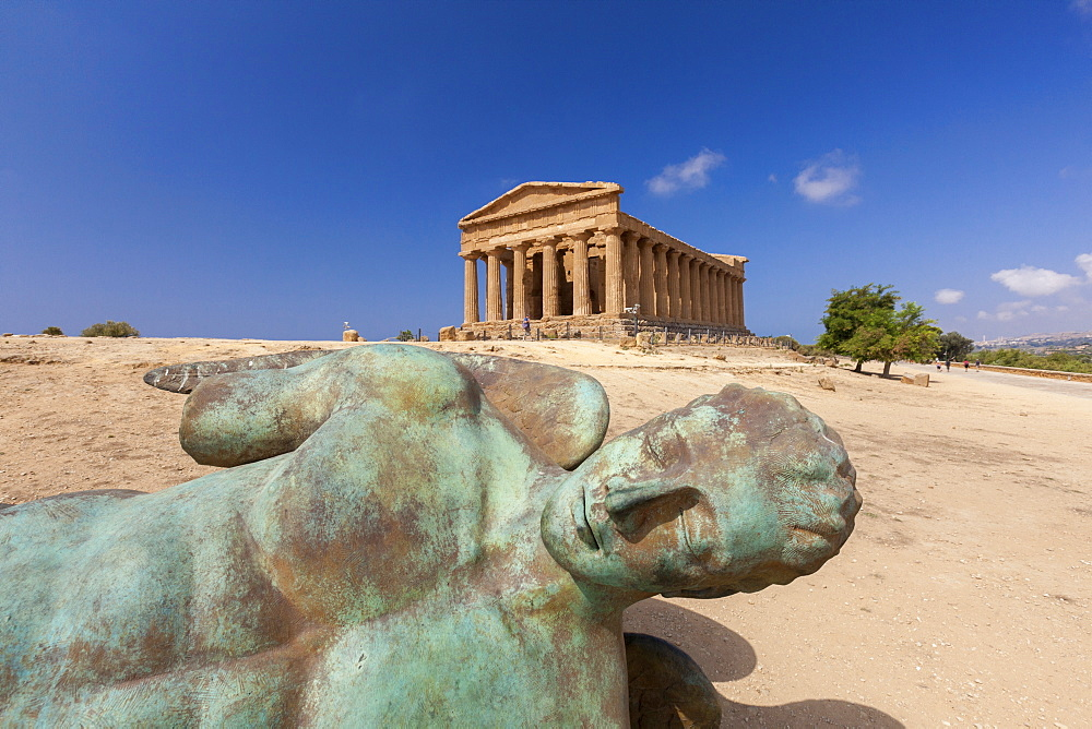 Bronze statue of the fallen Icarus frames the ancient Temple of Concordia Valle dei Templi Agrigento Sicily Italy Europe