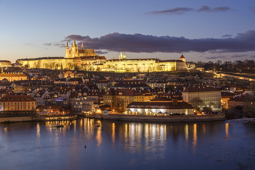 View of the Vltava River framed by historical buildings at dusk, Prague, Czech Republic, Europe