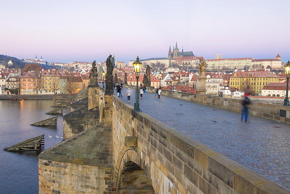 People on the historical Charles Bridge on Vltava River at dawn, UNESCO World Heritage Site, Prague, Czech Republic, Europe