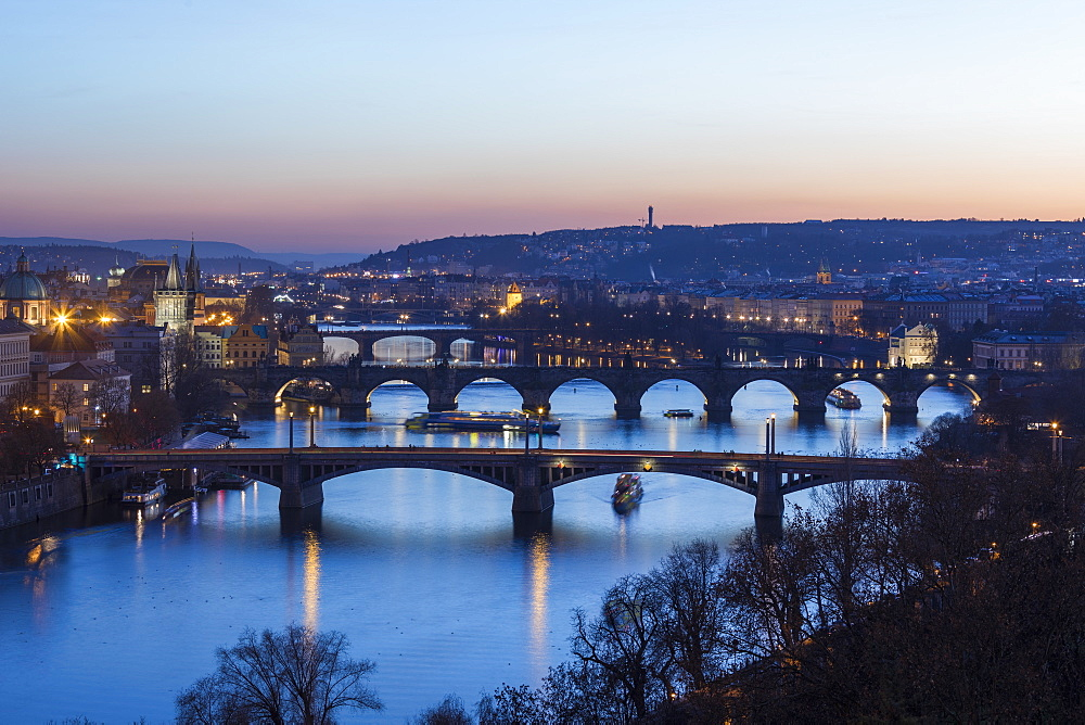 Dusk lights up the historical bridges and buildings reflected on Vltava River, Prague, Czech Republic, Europe