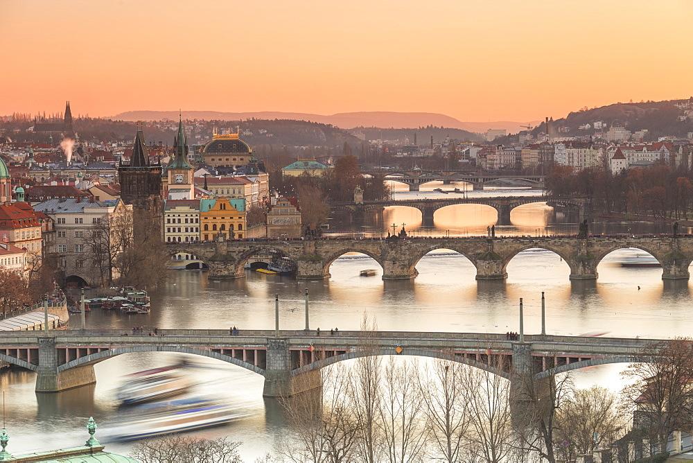 Orange sky at sunset on the historical bridges and buildings reflected on Vltava River, Prague, Czech Republic, Europe