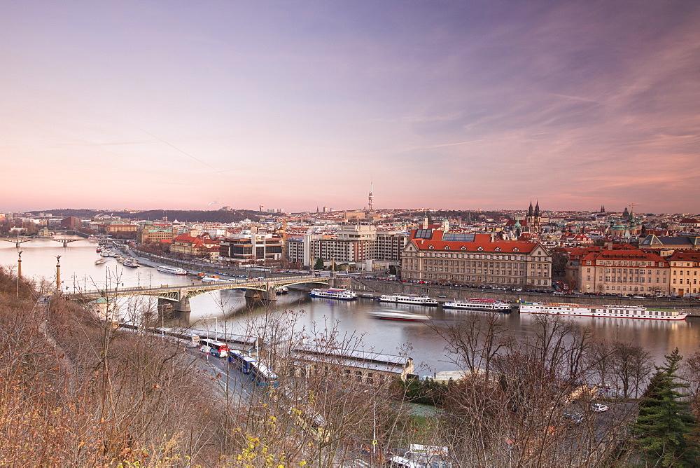 Pink sky on historical bridges and buildings reflected on Vltava River at sunset, Prague, Czech Republic, Europe