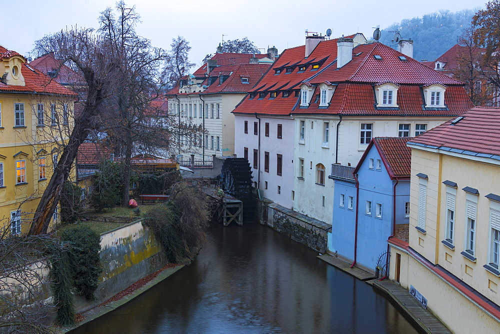 Typical houses on water canal frame the old mill of Certovka, Lesser Quarter, Prague, Czech Republic, Europe
