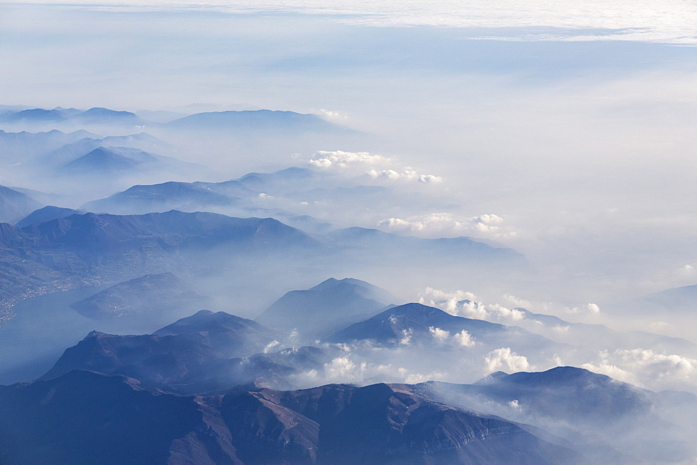Aerial view of the profile of the mountain peaks surrounded by mist, Orobie Alps, Lombardy, Italy, Europe